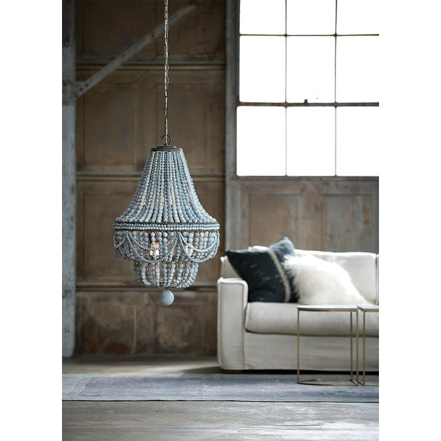 Classic style meets modern charm with this chandelier. A bevy of draped weathered blue wooden beads, dresses up the steel...