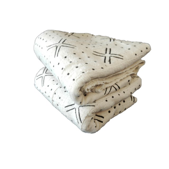 Superb set of two white and black mud-cloth cotton fabrics, handwoven, hand-sewn, and hand-dyed by the men and women of...