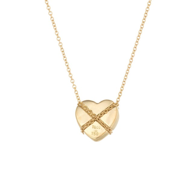 Elegant and finely detailed vintage Tiffany & Co Cross My Heart necklace, crafted in 18 karat yellow gold. The necklace is...