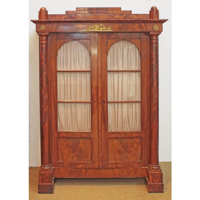 A 19th Century Biedermeier bibliotheque of mahogany with column side supports, bullet finials and a stepped top, the whole...