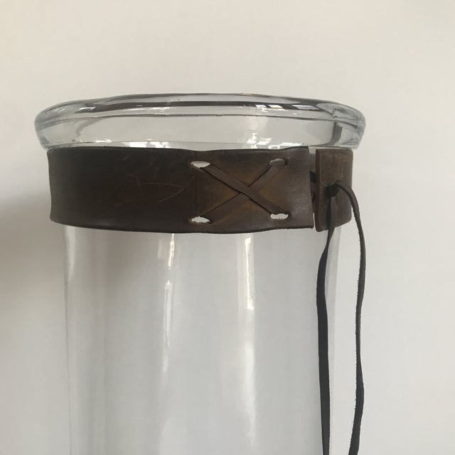 """Tall blown glass vase with rustic leather """"collar"""" detail. Thick turned rim at top. Leather piece can easily be removed...."""