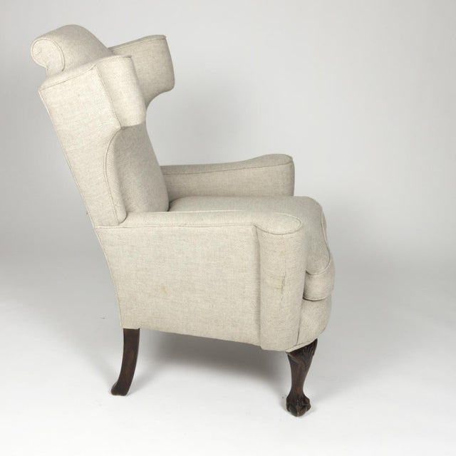 A classic large-scale English wing chair with mahogany frame, carved mahogany legs with shell carving at the knee and...