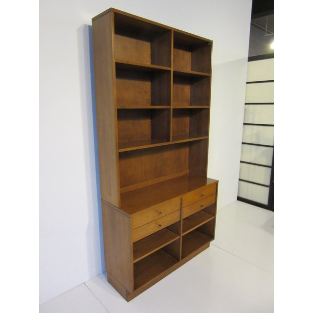 A maple two piece McCobb bookcase sitting on a smaller chest with two drawers and brass T pulls . The upper case has fixed...