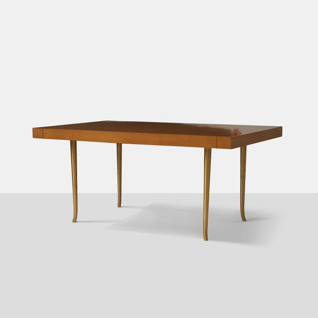 A dining table in Italian walnut with two end-mounting leaves siting atop four slightly sabred legs in spun brass....