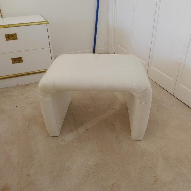 Elegant and timeless 'Dansen' ottoman. A soft off white color fabric believed to be a thick cotton. Upholstery has some...