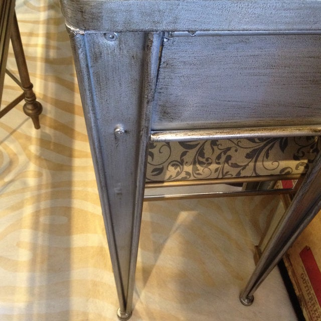 Four drawers add to the infinite usability of this console table. Love the antique silver vintage look. Made of metal....