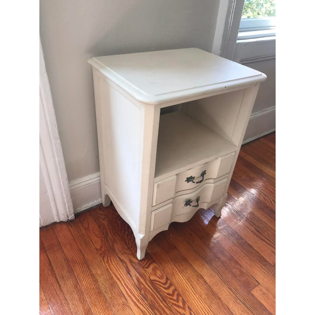 Vintage French distressed nightstand. Hand painted in a soft white. Two drawers with original hardware, one of which needs...