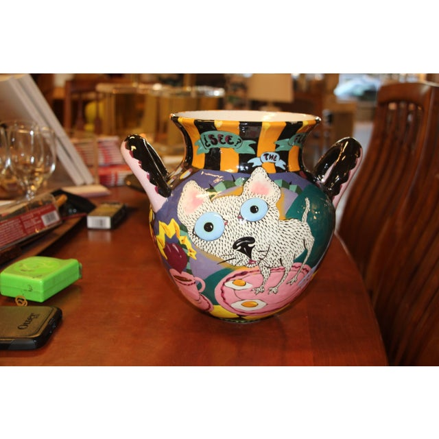 A whimsical Glazed hand done pot featuring a cat on a pan with eggs on one side and jumping up in alarm on the other side....