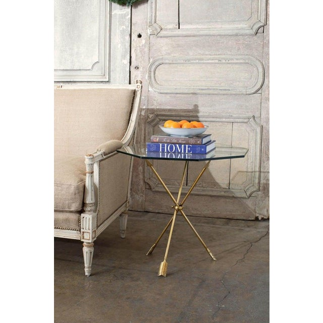 Stunning pair of brass directore neoclassical style arrow tripod tables made in the manner and style of Maison Jansen....