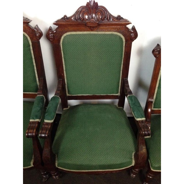 Set of four Rococo Revival carved and veneered mahogany dining chairs. Comprised of two armchairs and two side chairs....