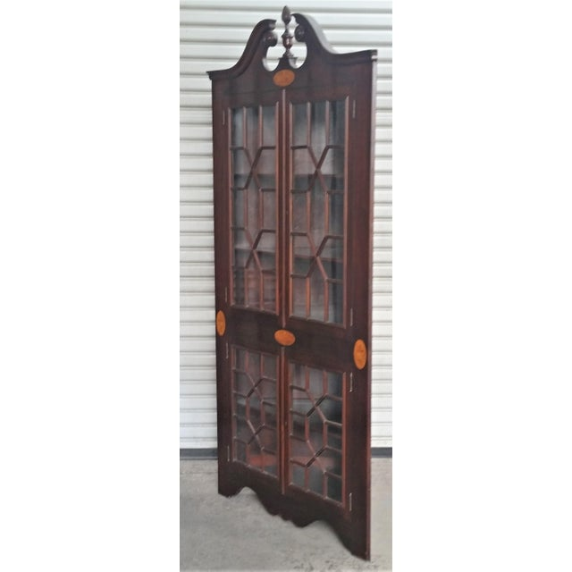 Wonderful mahogany corner cabinet. Beautiful medallion inlays. Broken arch pediment with fluted finial. The doors have a...