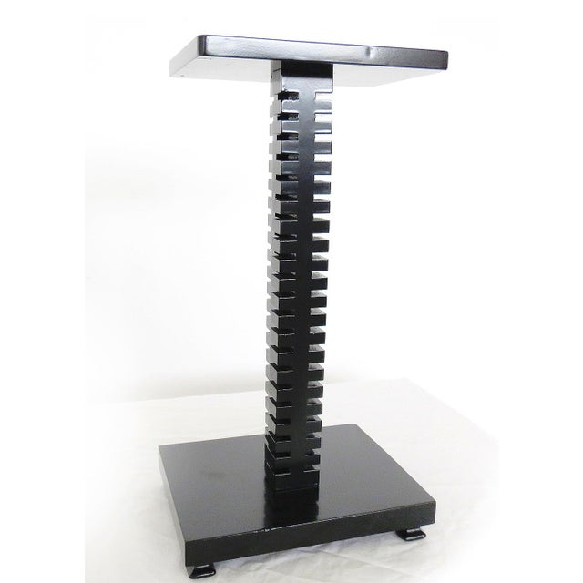 This black smoking stand features a spine-like column, giving this small-scale piece major character.