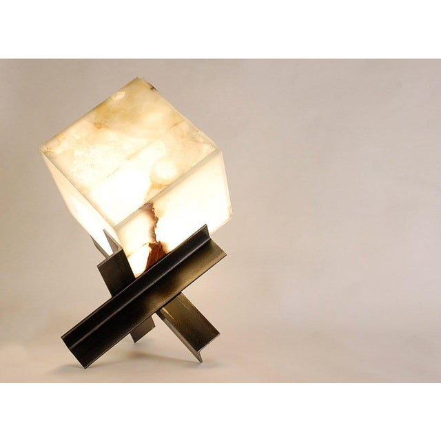 The sculptural 'Cubyx' lamp is made of a jointed translucent onyx panel cube placed on a tripod base. The bulb is changed...