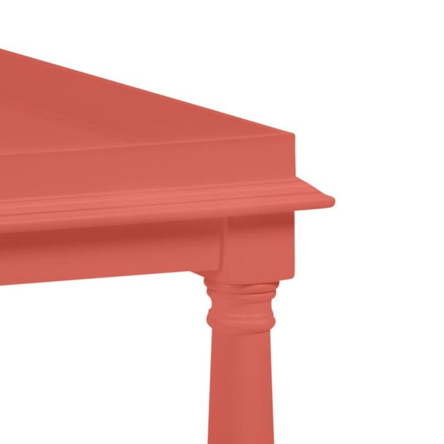 Made of acacia wood, this cocktail table features a gallery shelf and turned legs. Color is Benjamin Moore Crimson with a...