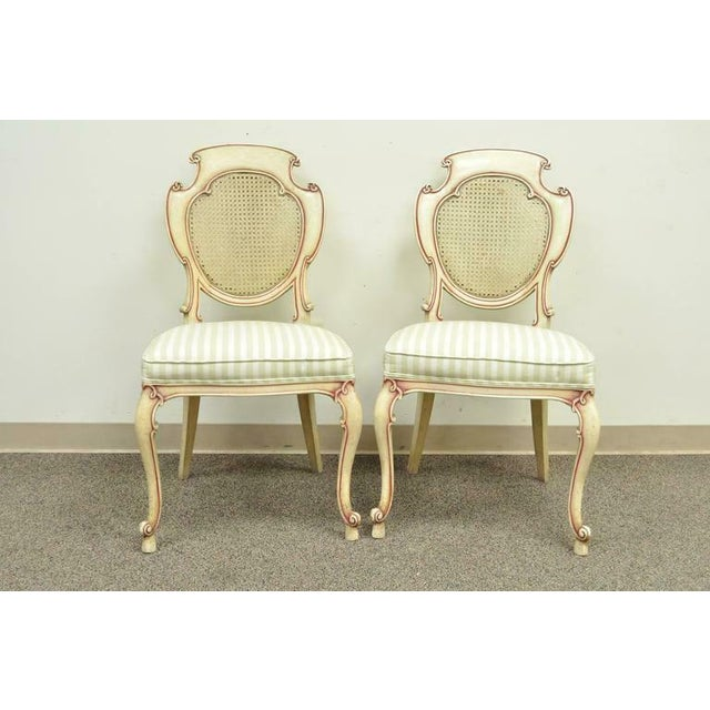 Very unique set of four vintage scroll carved Italian Hollywood Regency cream and pink painted side chairs. Items feature...