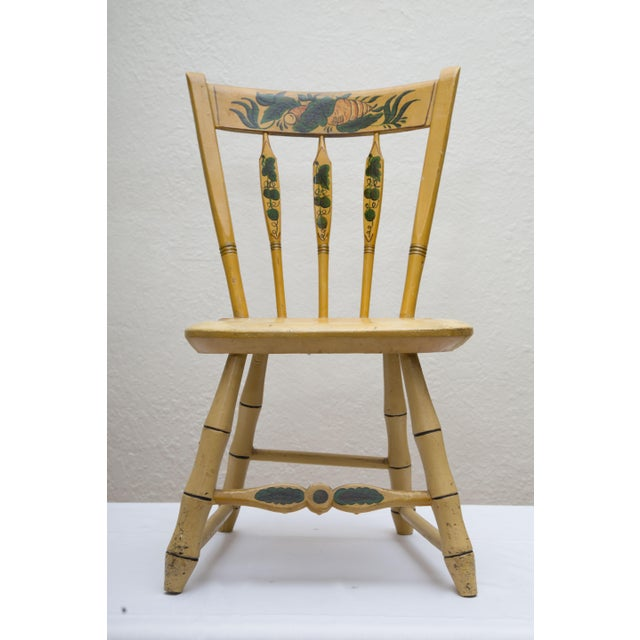 This is a butter yellow painted and stenciled child chair offering the Ambience of New England charm, circa 1880-1900.