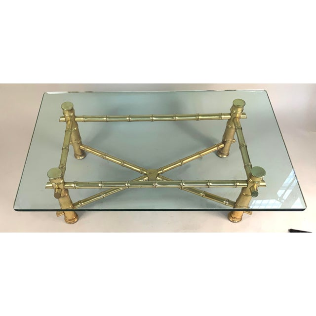 A vintage 1960s gilded wood frame coffee table made to resemble bamboo, with a very thick glass top. Beautiful design and...