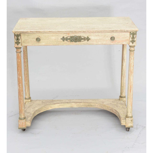French Empire console table, having distressed painted finish, single frieze drawer, bronze medallions on drawer and atop...