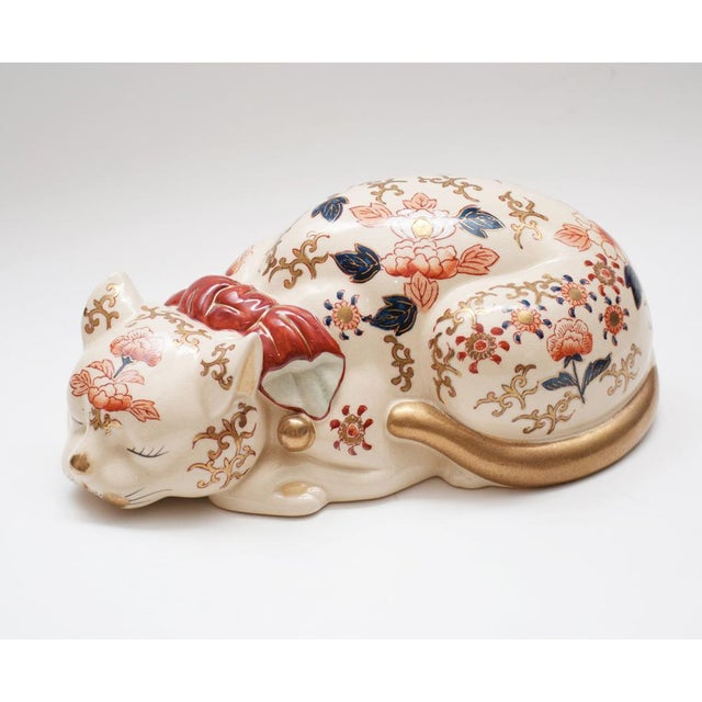 Japanese Imari Nemuri-neko figurine with a red collar and gold bells. Made of cream porcelain with a crackled glaze and...