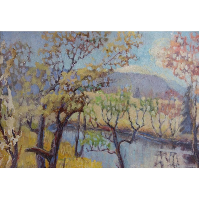 This is a framed vintage oil on canvas painting of a wooded landscape with a river during the fall season. It is signed...