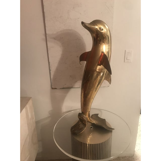 This shiny gold brass dolphin is a great size at 32 inches tall and the patina shines but shows true vintage age with some...