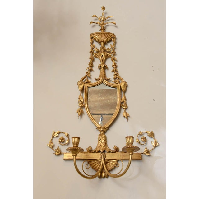 Pair of giltwood sconces, in classical form, each surmounted by carved fluted flower-filled urn draped with swags, shield...
