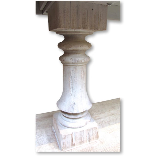 A large scale wood console table with dual carved pillar base and lower shelf features a distressed white washed finish,...
