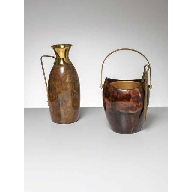 Rare set of ice bucket and pitcher by Aldo Tura. Brass pins and cork accessories and shiny parchment finish.
