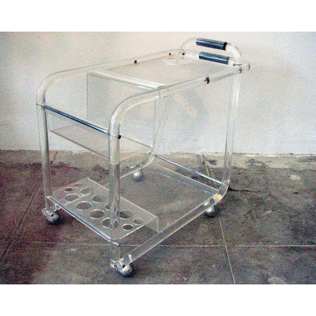 This Mid-Century Modern bar cart in Lucite features two tiers with plenty of built-in storage including inset holes for...