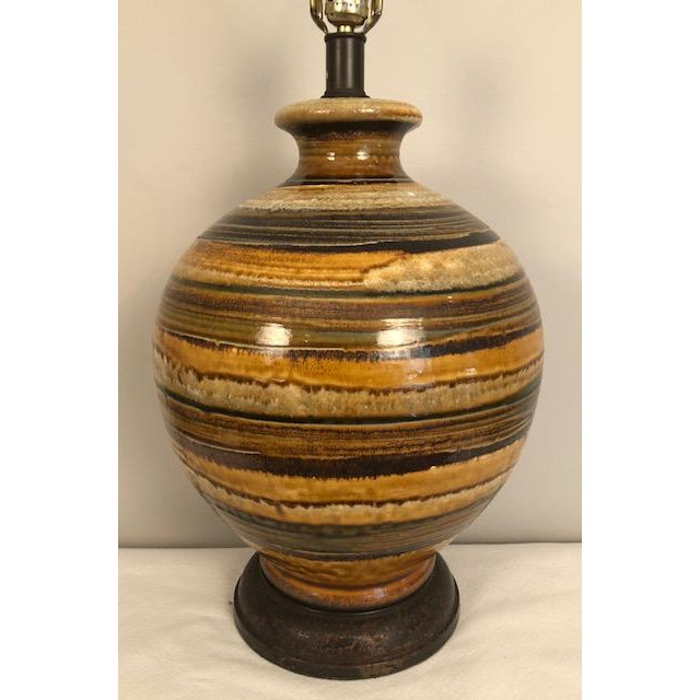 A large mid-century modern volcanic lava glazed ceramic table lamp is available for sale. The large globe-shaped body is...