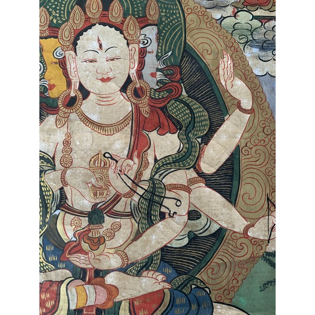 This ornate and colorful Thangka depicts a ceremonial image, hand painted by Buddist monks and is surrounded by a woven...