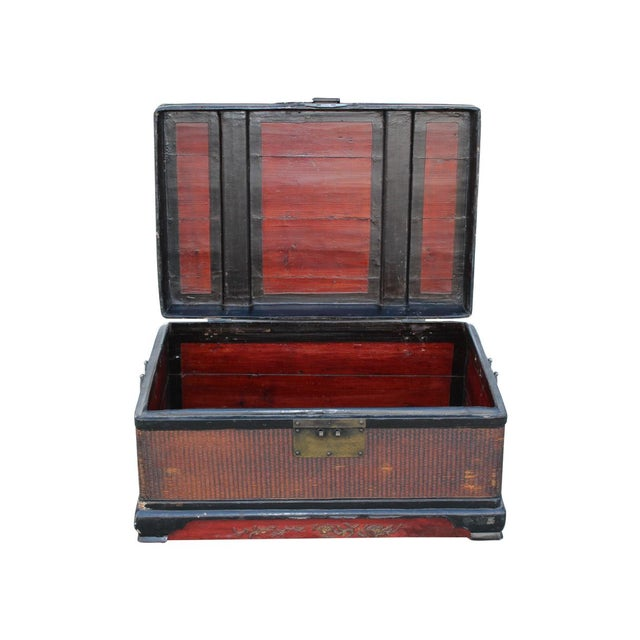 Offered is a vintage red and black wood Chinese trunk with brass handles and clasp closure.
