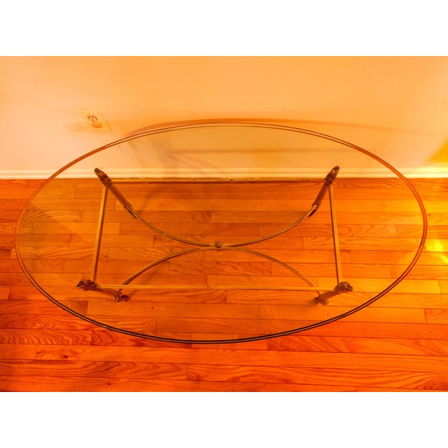 "This elegant, Hollywood Regency coffee table La Barge Style has a clear, oval 3/4"" beveled glass top and a curved brass..."