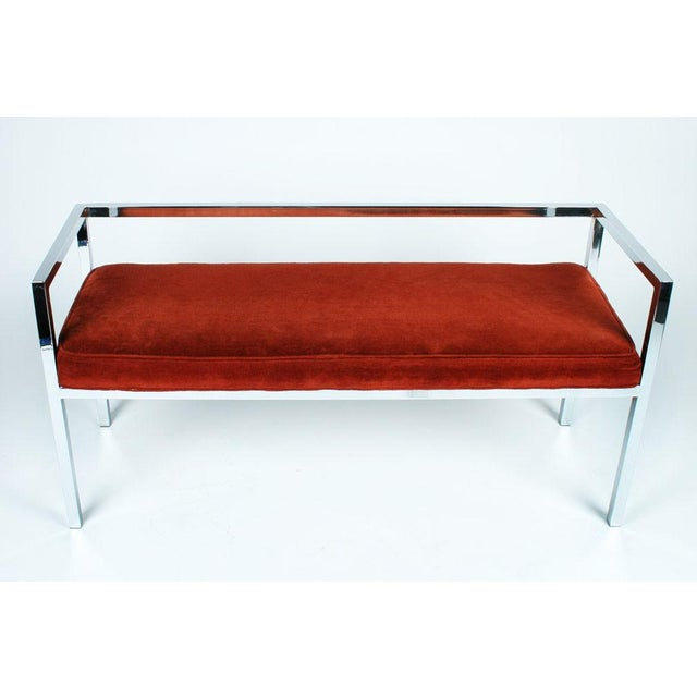 A polished chrome steel entry bench in a square tube, open back and arms frame with an attached upholstered seat. With...