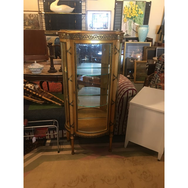 Gilt french Louis XVI vitrine. Bowed glass doors and sides. Mirrored back.