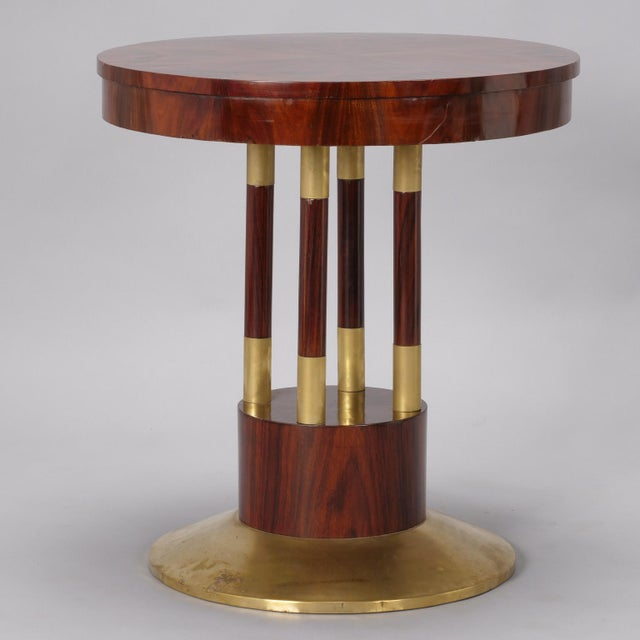 Circa 1910 round pedestal center table has solid brass base and beautifully grained rosewood top. Four support columns...