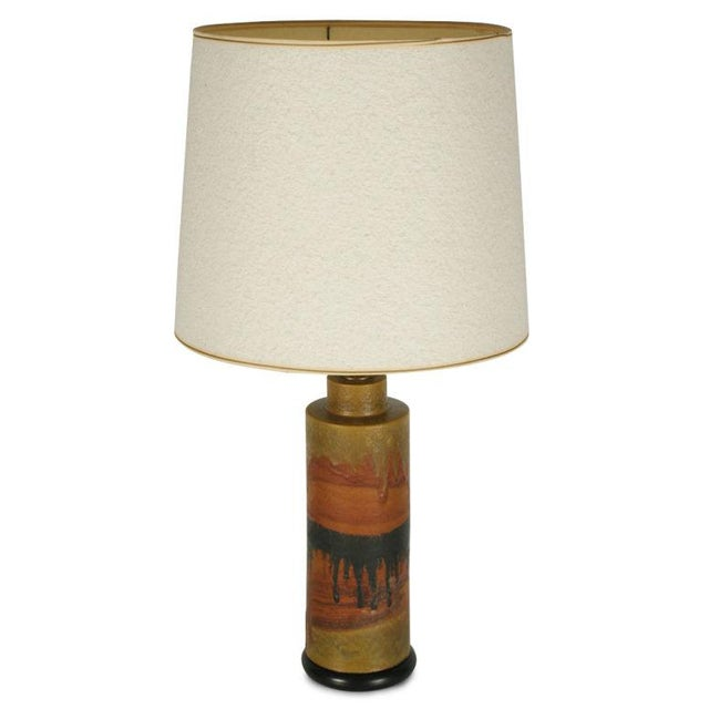 A column shaped ceramic table lamp on a wood base with turned brass neck and a painterly drip glaze body reminiscent of a...