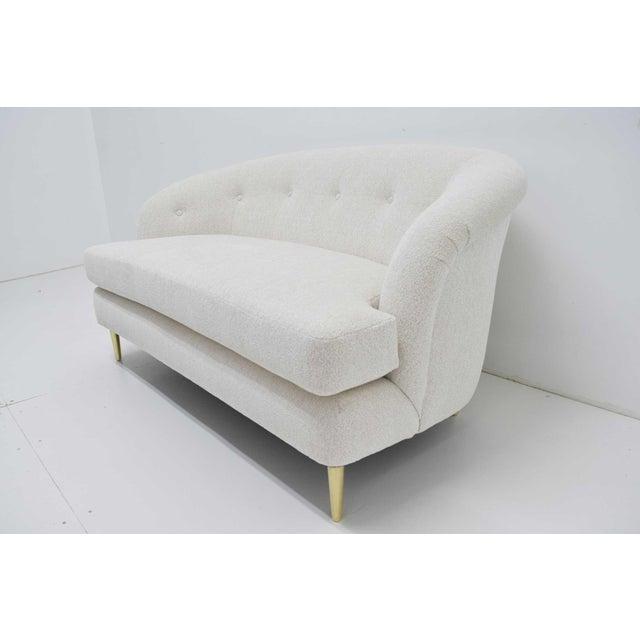 Beautifully restored Dunbar short sofa with brass legs. New upholstery by Larsen.