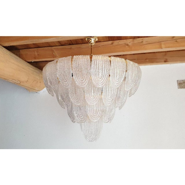 Large vintage translucent clear and textured Murano glass chandelier, with a gold-plated frame and chain. The Mid-Century...