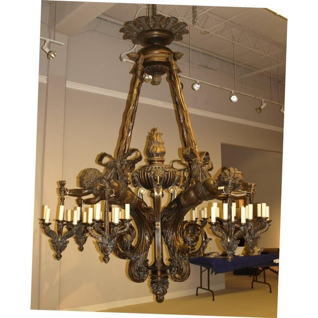Magnificent bronze and carved wood chandelier featuring four cherubs holding smaller stylized chandeliers in each hand, 48...