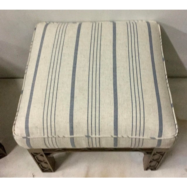 Pair of newly upholstered Chinese Chippendale style ottomans in a new ivory and blue striped linen. The frame is a carved...