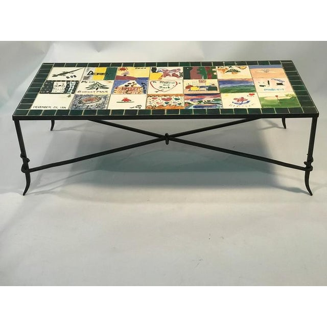 A whimsical, ceramic tile top co ee or cocktail table with iron X-base . Colorful, hand-painted, nostalgic scenes, signed...