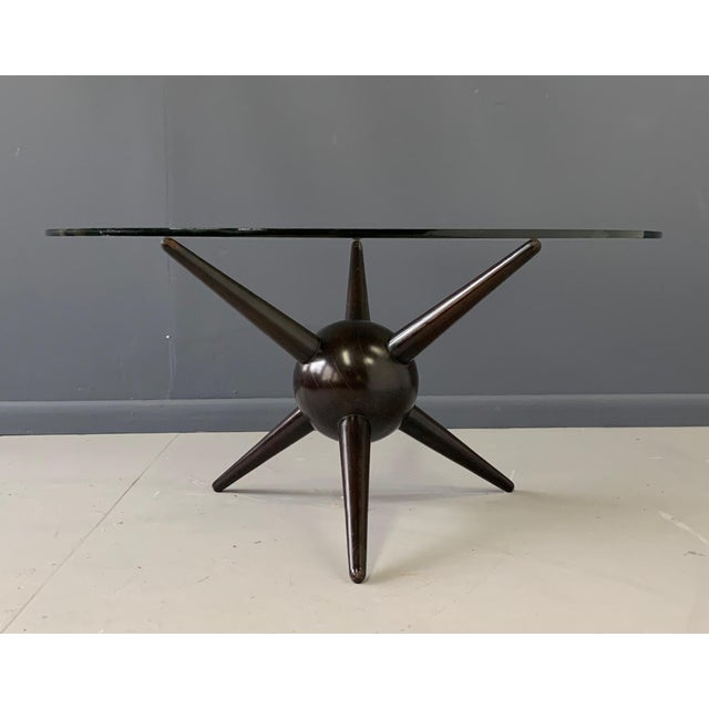 Wonderfully designed coffee table looking like a satellite in motion is made of solid walnut wood pieces with a dark stain...