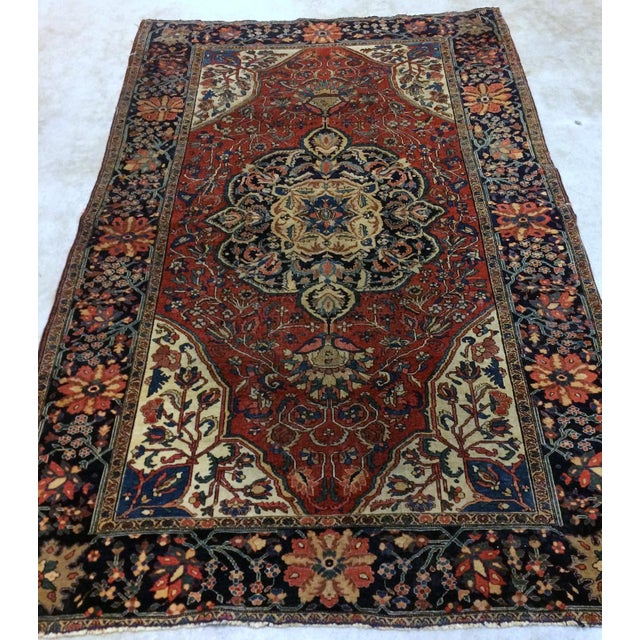 Handmade antique Persian Sarouk Farahan rug in original good condition in deep shade of red. The rug made out of wool and...