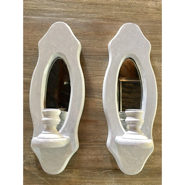 Offered is a pair of wood oval shaped grey painted mirrored candle sconces. Made in USA.