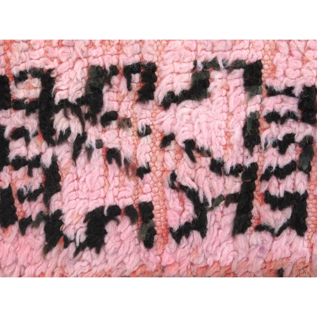 Vintage Boujad rug handwoven with pale pink, soft coral, and black wool in an abstract design and Berber symbols....