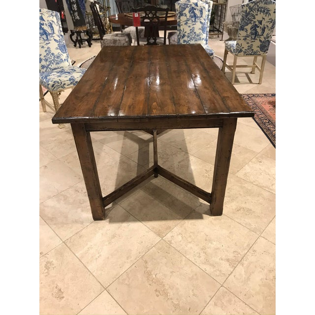 A beautiful Guy Chaddock wood dining table with plank top.This table features a distressed wood look with a high gloss...