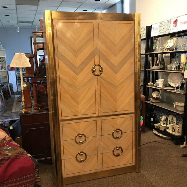 Mastercraft tall wardrobe with patinated brass details. Striking parquetry zebrano wood front in a zig zag pattern. Three...
