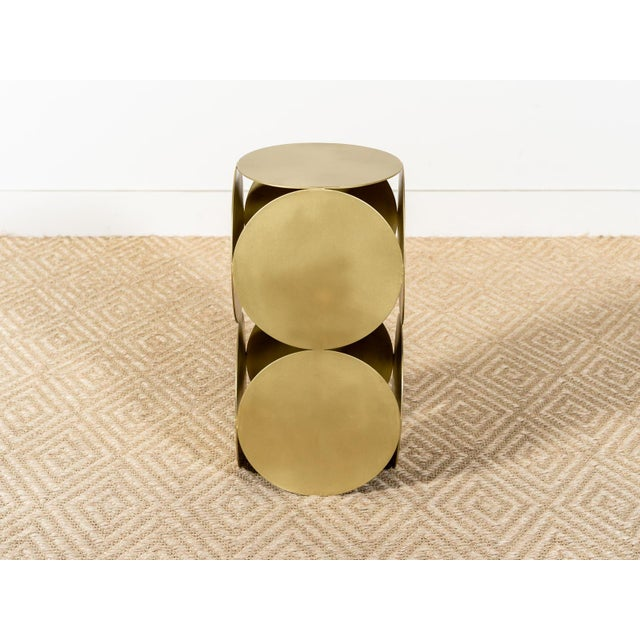 Sculptural side table Constructed of metal disks in Antique Brass finish Natural variation in tone and luster will occur