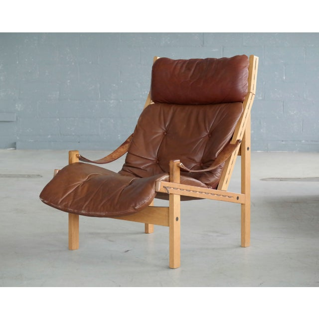 """Classic safari style high back easy chair model """"Hunter"""" in oak and leather designed by Torbjørn Afdal in the late 1960s..."""